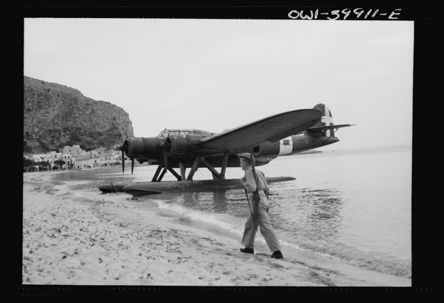 An Italian seaplane on the Sicilian beach guarded by a British soldier
