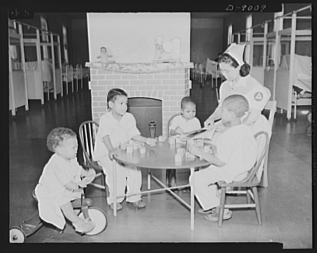 Answering call for volunteer nurses aides. At Freedmen's Hospital, Washington, D.C., senior aide Beleno is shown entertaining four convalescent infant patients. A regular graduate nurse is relieved from this duty
