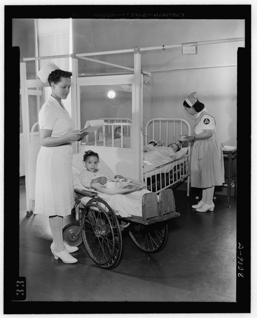 Answering call for volunteer nurses aides. Freedmen's Hospital, Washington, D.C. Senior aide Louise Beleno assists staff nurse Vashti Hall in the care of the patients. Nurse Hall is shown holding food cart, while Aide Beleno feeds another patient