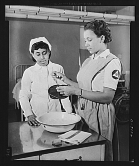 Answering call for volunteer nurses aides. Miss Thelma Harris, instructor of volunteer nurses aides at Freedmen's Hospital, Washington, D.C., gives Miss Maxine Jackson directions on how to fill an ice cap. Miss Jackson is one of the many volunteers now being trained at the hospital