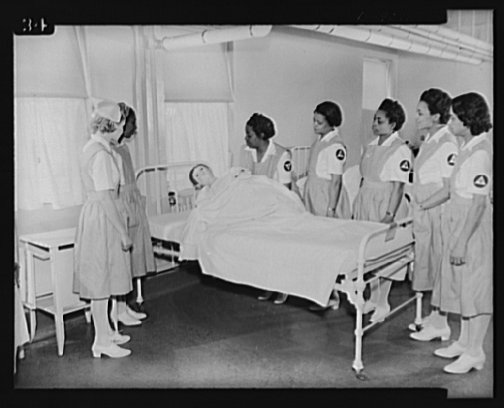 """Answering call for volunteer nurses aides. Mrs. George M. Johnson, captain, instructing volunteer nurses aides in the handling of patients at Freedmen's Hospital, Washington, D.C. using """"Julius Caesar"""" as dummy patient. Left to right: Mrs. Johnson, Mrs. Amontha Dawkins, Miss Florence Jackson, Mrs. Mary F. Anderson, Mrs. Estelle Cloggette, Mrs. Mary Hobson"""