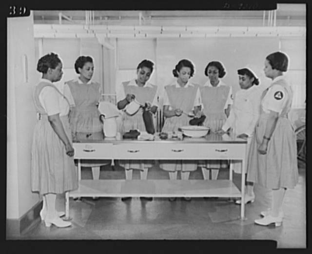 Answering call for volunteer nurses aides. One phase of training for the volunteer nurses aides at Freedmen's Hospital, Washington, D.C.  Miss Thelma Harris, staff nurse, is shown instructing uncapped students on how to fill hot water bottles and ice caps. Left to right: Miss Florence Jackson, Mrs. Maxine Jackson, Mrs. Estelle Cloggette, Mrs. Mary Hobson, Mrs. Samontha Dawkins, Miss Thelma Harris and Mrs. Mary F. Anderson