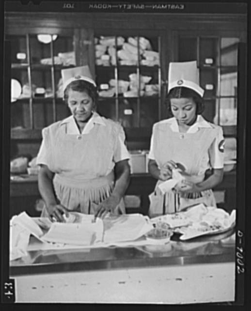 Answering call for volunteer nurses aides. The call for 100,000 volunteer nurses aides to relieve the acute shortage of graduate nurses is answered by Negro housewives and mothers throughout the country. At Freedmen's Hospital in Washington, D.C. where an eighty-hour training courses has been in progress since last October. Volunteers begin practical training in the central dressing room. Photo shows Mrs. Louis Lucas (left) and Miss Susie Freeman (right) wrapping bandages