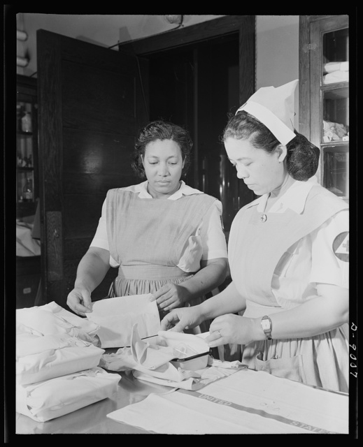 Answering call for volunteer nurses aides. The central dressing room at Freedmen's Hospital, Washington, D.C., Mrs. Ethel Washington and Mrs Louise Beleno, senior aide, packing surgical kits as part of work of volunteer nurses aide class. These volunteers help relieve the shortage of graduate nurses