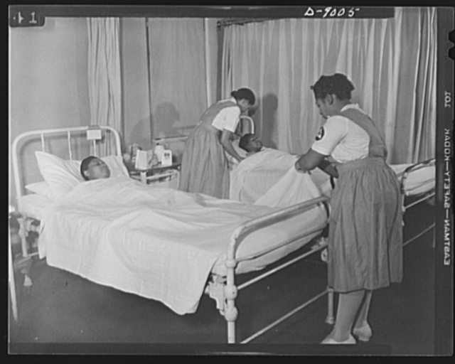 Answering call for volunteer nurses aides. Volunteer nurses aides assist graudate nurses by making and changing beds. Photo taken in women's surgical ward of Freedmen's Hospital, Washington, D.C., showing volunteer nurses aide, Miss Romay Johnson (left) and Mrs. Dora Boston (right) changing bedsheets for patients