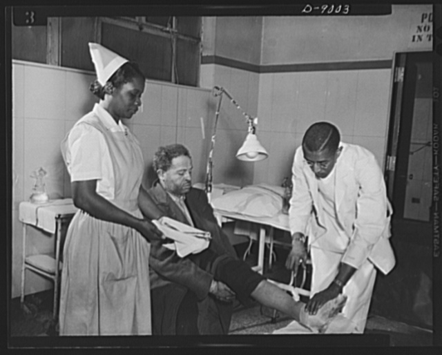 Answering call for volunteer nurses aides. Working always under supervision of a graduate nurse or physician, volunteer nurses aides help out in emergency cases. Photo shows Dr. Granville N. Moore and Miss Florence Grant, volunteer nurses aide, attending a patient in the emergency operating room of Freedmen's Hospital, Washington, D.C.