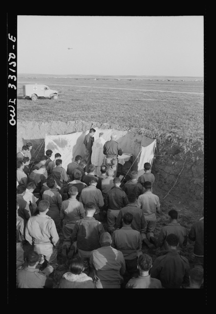 """Archbishop Francis J. Spellman of New York touring the North African battle front, saying a mass for the men at the 57th Fighter Group of the U.S. Army 9th Air Force. This group, located """"somewhere in Tunisia,"""" knocked almost 100 Axis transports and fighters out of the skies in one engagement"""