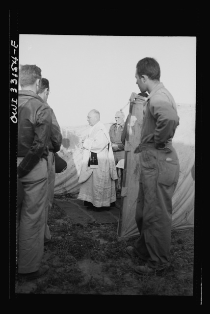 "Archbishop Francis J. Spellman of New York touring the North African battle front, saying mass for the men at the 57th Fighter Group of the U.S. Army 9th Air Force. This group, located ""somewhere in Tunisia,"" knocked almost 100 Axis transports and fighters out of the skies in one engagement"