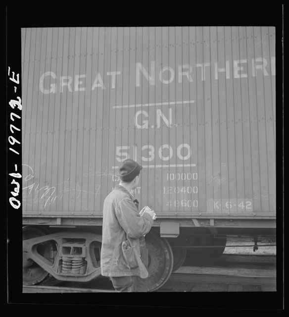 Argentine, Kansas. A brakeman checking the car numbers of his Atchison, Topeka and Santa Fe train before pulling out of the railroad yard between Argentine and Emporia, Kansas