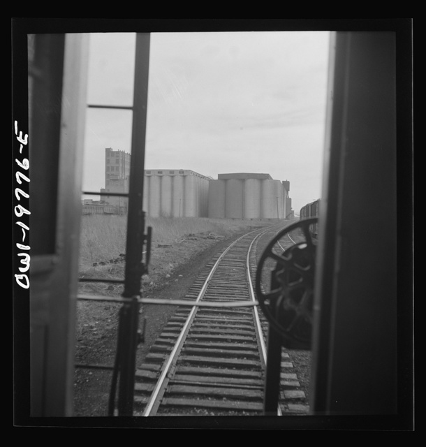 Argentine, Kansas. Atchison, Topeka, and Santa Fe Railroad train pulling out of the railroad yard, past the giant grain elevator