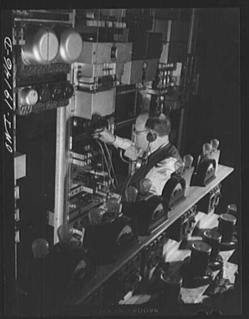 Argentine, near Kansas City, Kansas. Checking the telegraph apparatus in the telegraph room of the Atchison, Topeka and Santa Fe Railroad office building