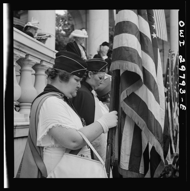 """Arlington Cemetery, Arlington, Virginia. American Legion color bearer listening to """"Taps"""" being played at the Memorial services in the amphitheater"""