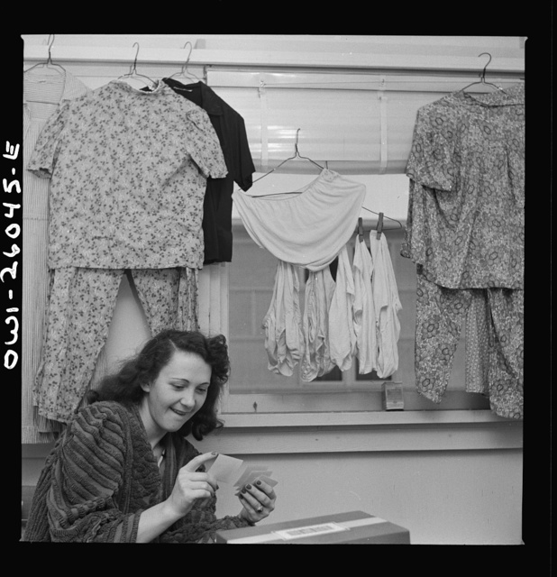 Arlington, Virginia. A girl looking at snapshots in her room at Idaho Hall, Arlington Farms, a residence for women who work in the U.S. government for the duration of the war. A typical room scene since there is a shortage of space in the laundries and authorities say that hanging the laundry outside will make the project look like a tenement