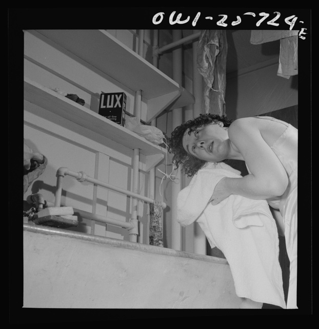 Arlington, Virginia. A girl washing her hair in a laundry tub at Arlington Farms, a residence for women who work in the government for the duration of the war