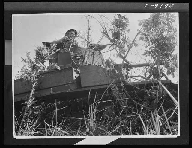Australia in the war. A member of an Australian tank crew awaits the signal for further attack from the hatch of a camouflaged American tank. This picture was made during the action at Buna