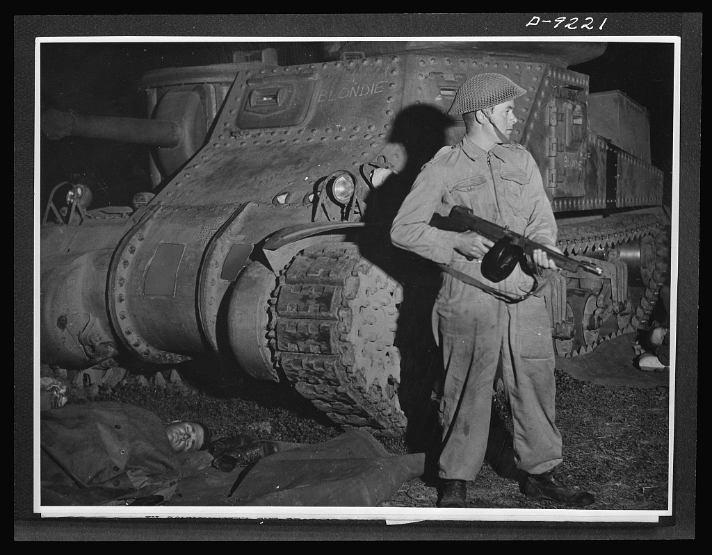 Australia in the war. American tanks and guns, provided under lend-lease, are performing a vital role in building up Australia's armored forces. This Australian member of a tank crew does his two-hour night watch with the aid of an American Tommy-gun