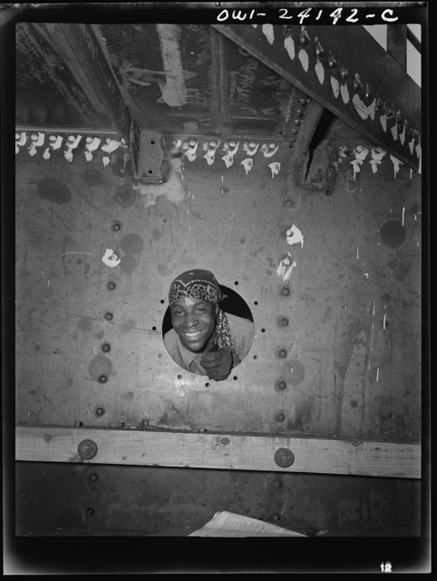 Baltimore, Maryland. Building the SS Frederick Douglass. More than 6,000 Negro shipyard workers are employed at the Bethlehem-Fairfield shipyards, where the Liberty ship is being rushed to completion. The noted orator and abolitionist leader worked as a ship caulker in the vicinity of this yard before he escaped from slavery. Smiling from porthole of the dock house is rivet heater Willie Smith