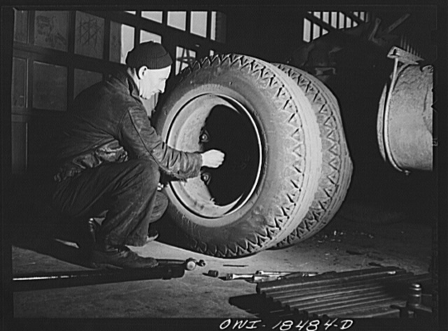 Baltimore, Maryland. Davidson Transfer Company trucking terminal. Loosening bolts to remove an axle rod in the truck service shop
