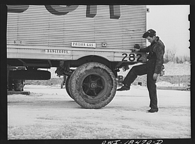 "Baltimore, Maryland. Davidson Transfer Company trucking terminal. ""Yard jockey"" checking over over a loaded trailer which is ready to go out on the road"