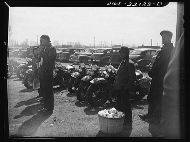 Baltimore, Maryland. Peanut and newspaper venders awaiting the three o'clock whistle outside the gates of the Bethlehem Fairfield shipyard. The parked motorcycles belong to the workers
