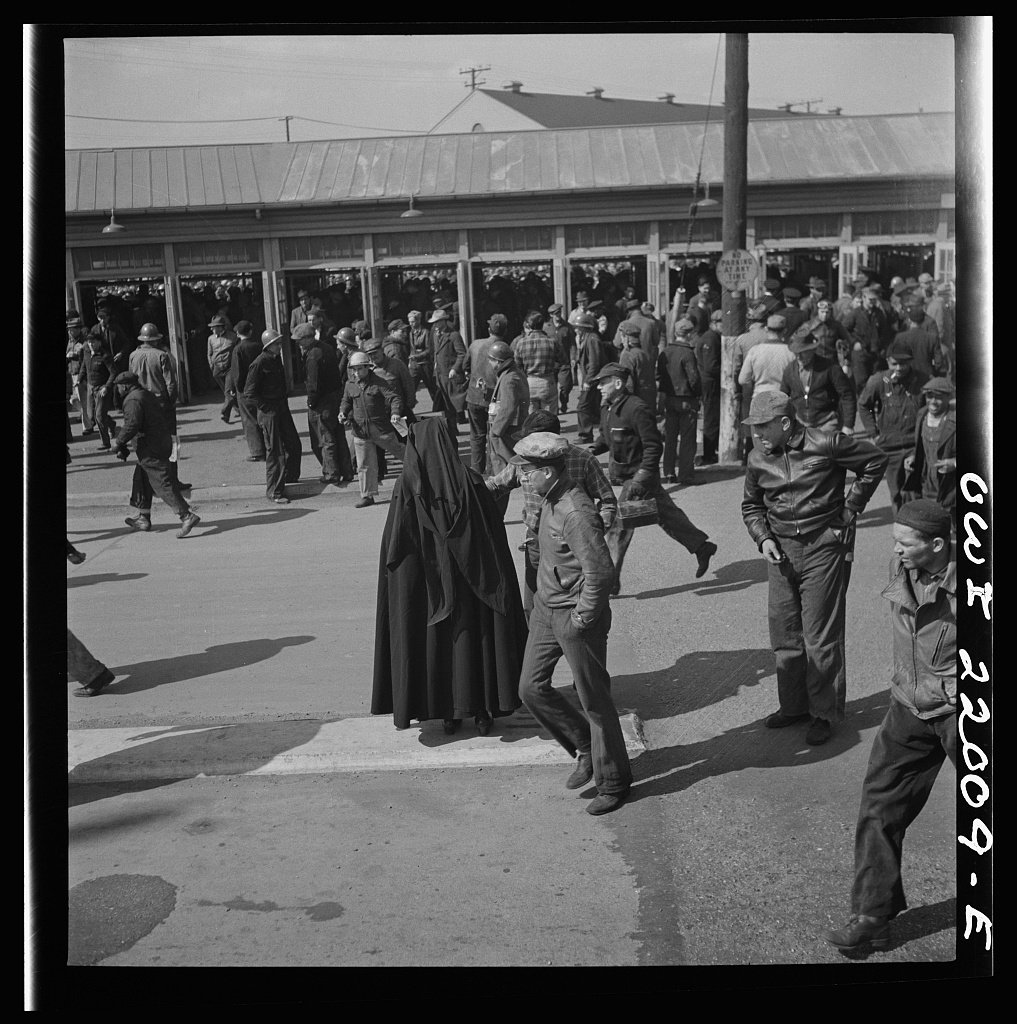 Baltimore, Maryland. Second shift workers leaving the Bethlehem Fairfield shipyard at three p.m. making a dash for cars, buses and trolleys. It is payday, and a Catholic sister awaits contributions