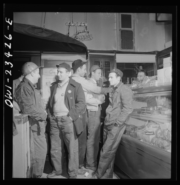 Baltimore, Maryland. Third shift defense workers waiting in a combination delicatessen and restaurant to be picked up by their car pools around midnight