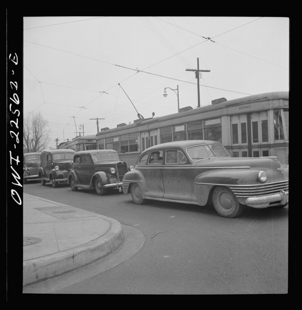 Baltimore, Maryland. Trolleys and cars leaving the Bethlehem Farifield shipyard on the road to Baltimore at three p.m. Workers are sharing the front car