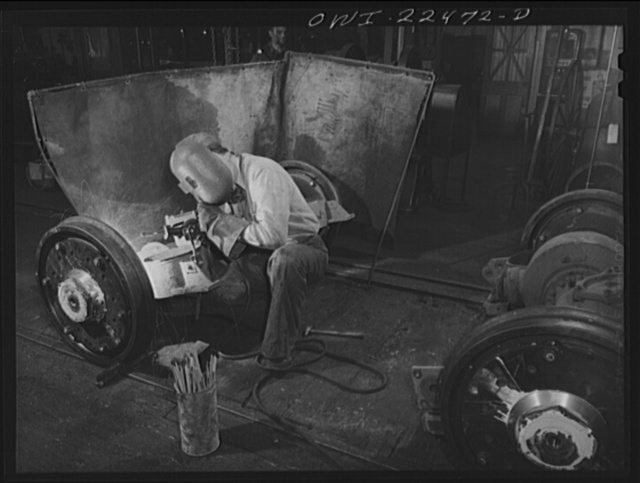 Baltimore, Maryland. Welding damaged steel plates which hold rubber sandwiches in the wheels of PCC trolleys at the machine shop of the Washington terminal, maintenance plant of the Baltimore Transit Company