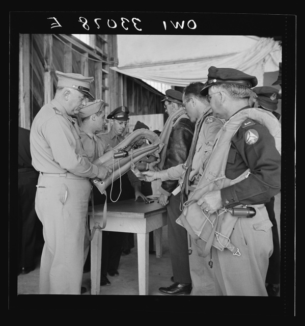 "Bar Harbor, Maine. Civil Air Patrol base headquarters of coastal patrol no. 20. Base commander Major James B. King making a routine inspection of ""Mae West"" life preservers"