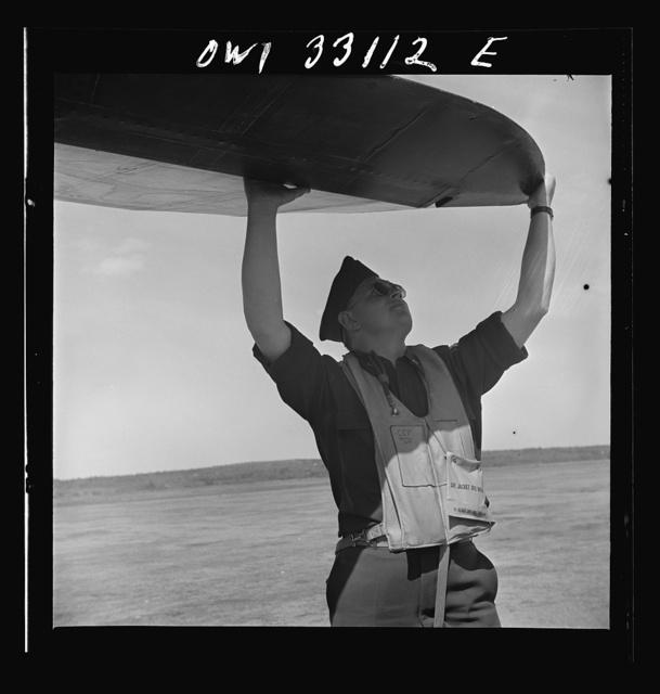 Bar Harbor, Maine. Civil Air Patrol base headquarters of coastal patrol no. 20. Pilot checking airplanes before taking off