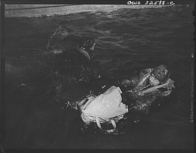 Bar Harbor, Maine. Civil Air Patrol base headquarters of coastal patrol no. 20. A flyer in an all-rubber crash suit testing the use of a rubber boat, which he is extracting from its bag