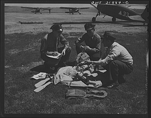 "Bar Harbor, Maine. Civil Air Patrol base headquarters of coastal patrol no. 20. Intelligence officer checking safety equipment issued to the pilot and observer of a patrol plane, including rubber boat and life jacket ""Mae West,"" inflatable by carbon dioxide gas cartridges; repair kit to mend bullet holes in the boat; and dye container to color water for better identification; flash light with red lens for identification by night; smoke bombs; water marker; Very pistols; and rubber watertight flying suit"