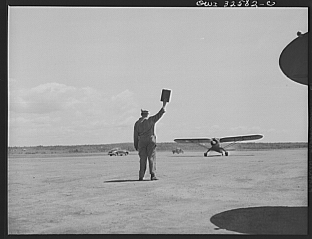 Bar Harbor, Maine. Civil Air Patrol base headquarters of coastal patrol no. 20. Ground crew directing a plane which is taxiing up to a gasoline pump after patrol duty