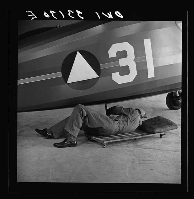Bar Harbor, Maine. Civil Air Patrol base headquarters of coastal patrol no. 20. Ground crew mechanic working on a patrol plane in the hangar