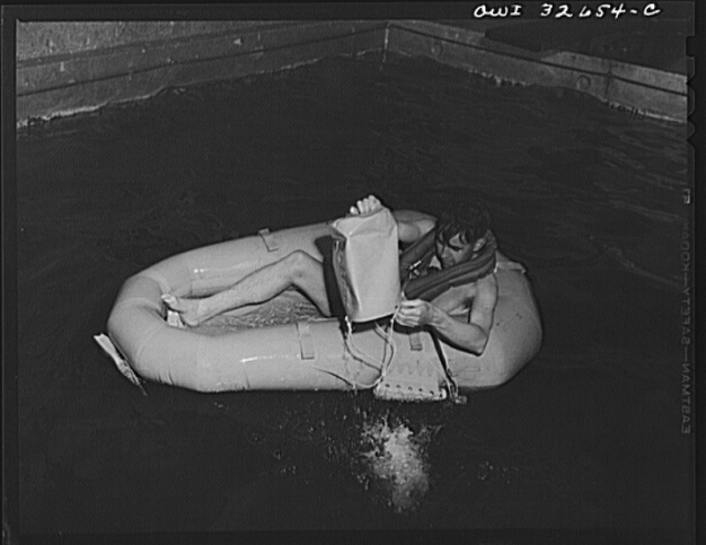 Bar Harbor, Maine. Civil Air Patrol base headquarters of coastal patrol no. 20. A flyer testing a rubber crash boat; he is bailing out the boat with a combination bucket and sea anchor