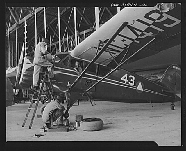 Bar Harbor, Maine. Civil Air Patrol base headquarters of coastal patrol no. 20. Ground crew marking a routine overhauling of a patrol plane
