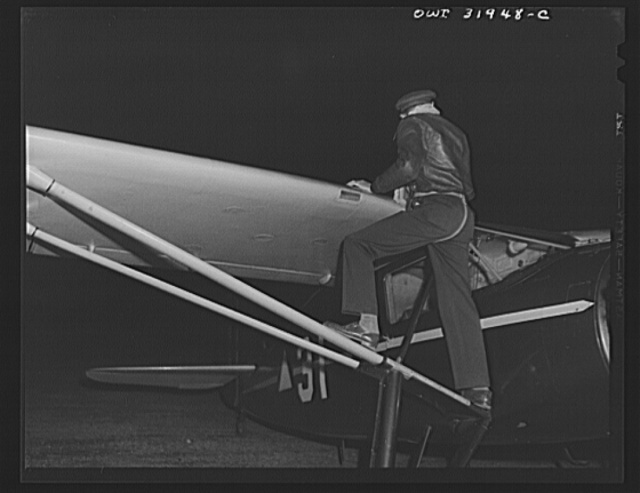 Bar Harbor, Maine. Civil Air Patrol base headquarters of coastal patrol no. 20. Pilot making a routine check on the gas supply before starting out on dawn patrol