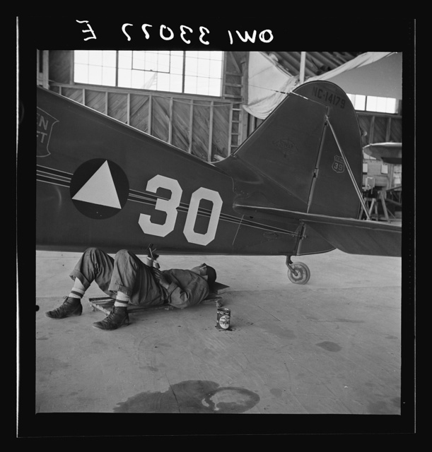 Bar Harbor, Maine. Civil Air Patrol base headquarters of coastal patrol no. 20. Ground crew working on a patrol plane in the hangar