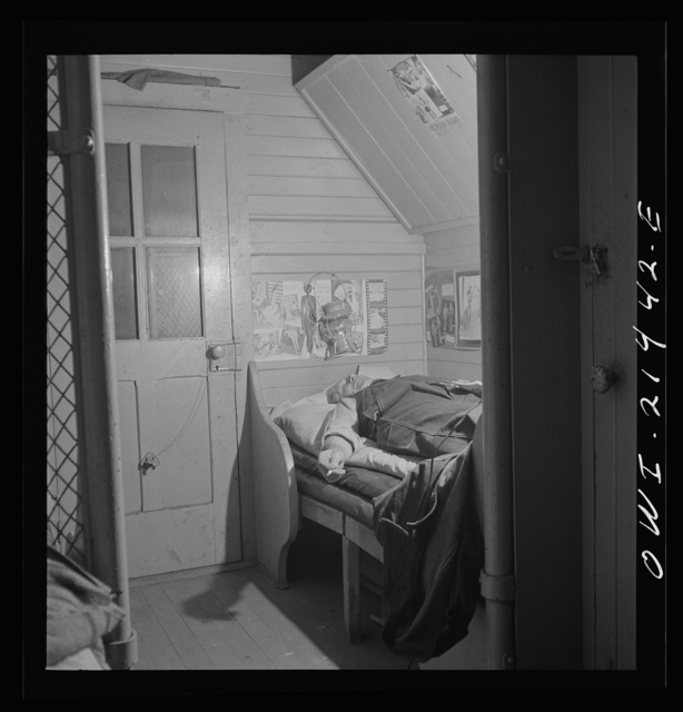 Barstow, California. A brakeman on the Atchison, Topkea and Santa Fe Railroad resting in his caboose at night