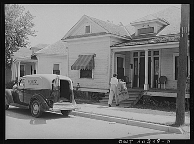 Beaumont, Texas. Elsie McMullen, a laundry truck driver, delivering material which has been drycleaned to a house