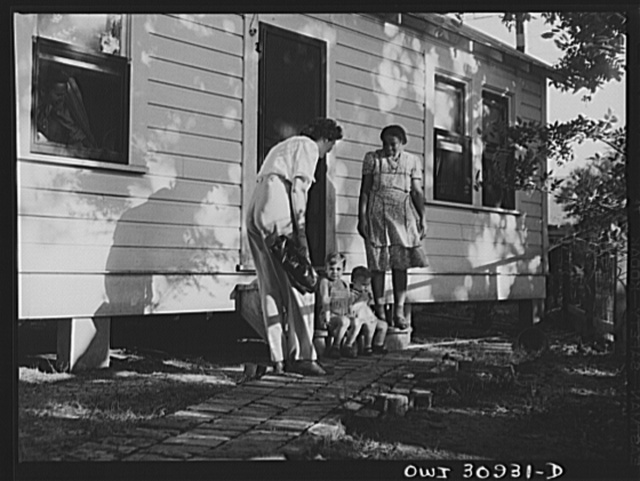 Beaumont, Texas. Mrs. Elsie McMullen, a laundry truck driver, returning home from work. A maid takes care of her children during the day