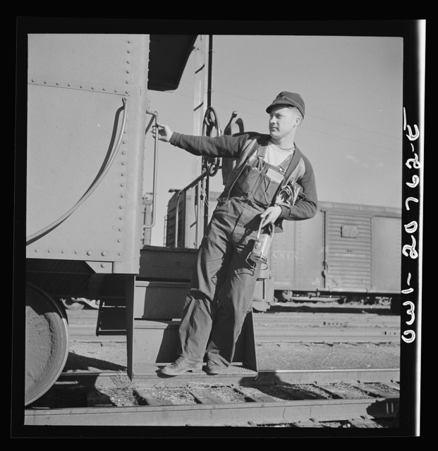 Belen, New Mexico. A brakeman on the Atchison, Topeka and Santa Fe Railroad C.G. Kirkland getting off the caboose