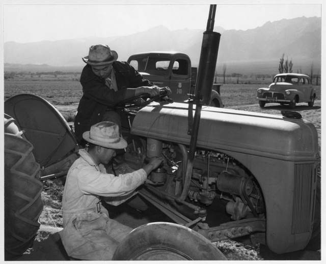Benji Iguchi and Harry [i.e., Henry] Hanawa, tractor repair, Manzanar Relocation Center, California / photograph by Ansel Adams.