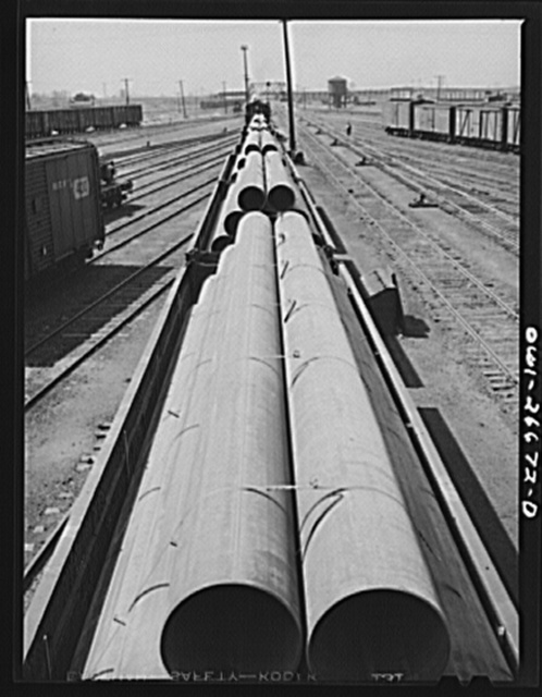 """Bensenville, Illinois. Pipe for the """"Big Inch"""" line, being switched at the Bensenville Yard for transfer to the eastern railroads by the Chicago, Milwaukee, Saint Paul and Pacific Railroad"""