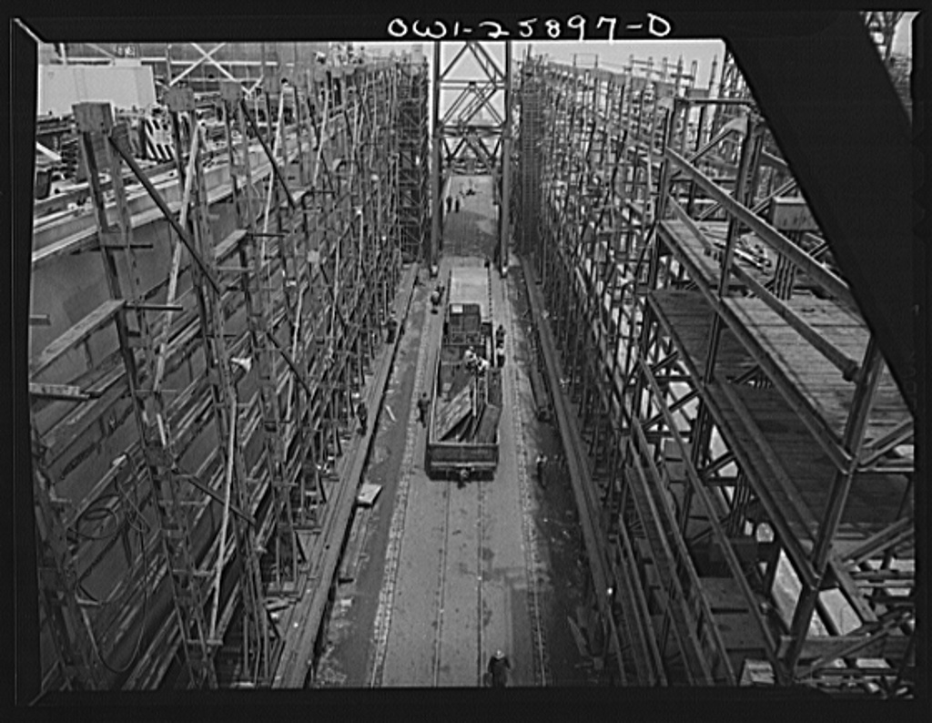 Bethlehem-Fairfield shipyards, Baltimore, Maryland. A freight car between two ways carrying steel sections of ship