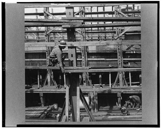 Bethlehem-Fairfield shipyards, Baltimore, Maryland. A shipyard worker erecting staging