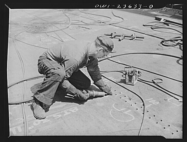 Bethlehem-Fairfield shipyards, Baltimore, Maryland. Beveling a bottom shell plating for welding