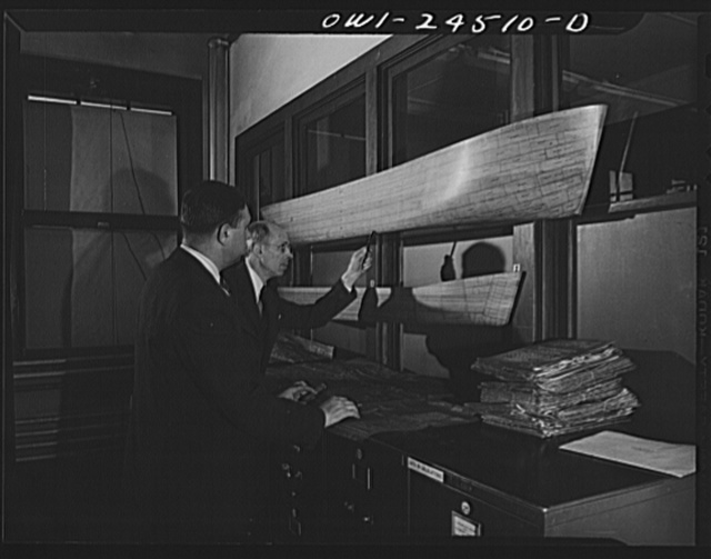 Bethlehem-Fairfield shipyards, Baltimore, Maryland. Discussing the model of a ship