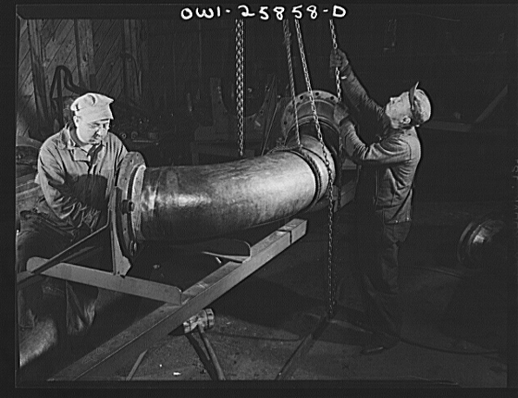 Bethlehem-Fairfield shipyards, Baltimore, Maryland. Fitting a flange on a huge pipe