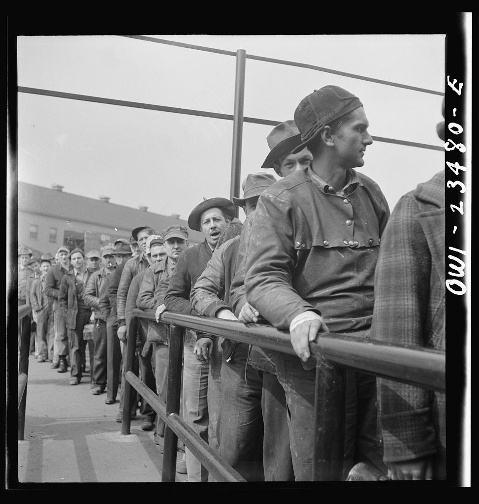 Bethlehem-Fairfield shipyards, Baltimore, Maryland. Lining up before a time clock at the changing of the shifts